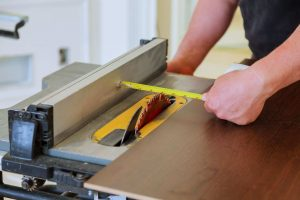 carpenter using table saw to cut plywood